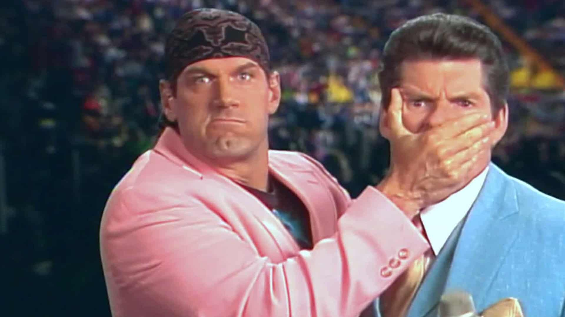 Jesse Ventura puts his hand over Vince McMahon's mouth