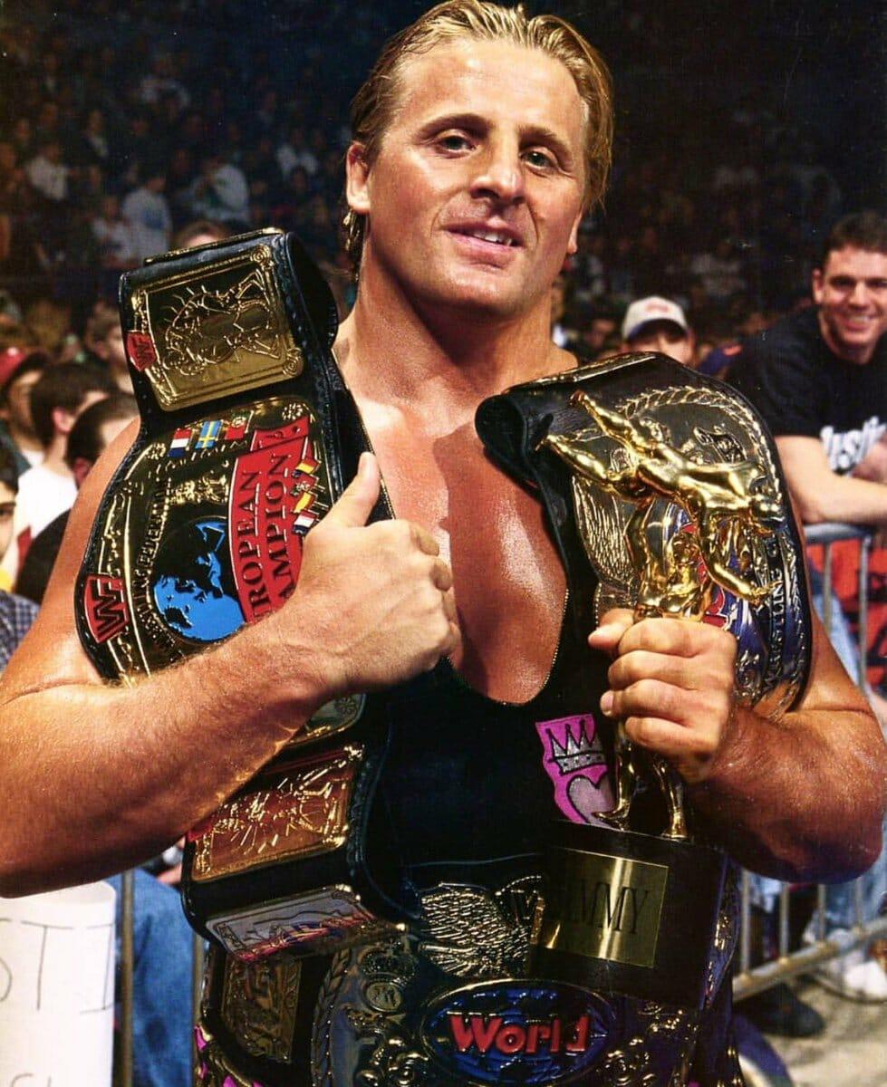 Owen Hart proudly displays his WWF European Championship, Tag Team Team Championship belts, and his Slammy award