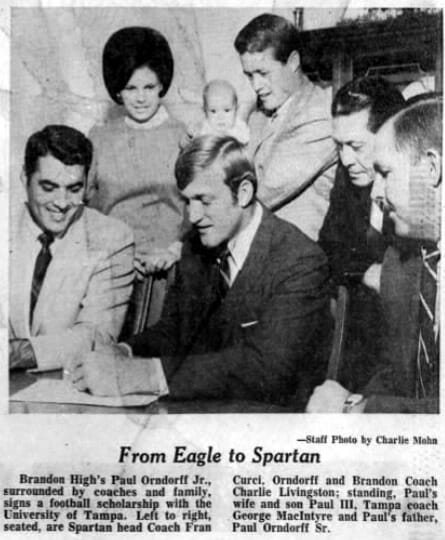 Paul Orndorff, surrounded by coaches and family, signs a football scholarship with the University of Tampa
