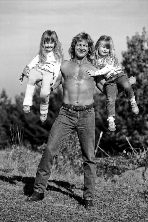 Roddy Piper got into the business of professional wrestling because he wanted a job that could provide for a family. Here, he poses with his daughters Anastasia Shea (age 5) and Ariel Teal (age 3) at his home on October 25, 1988, in Hillsborough, Oregon. (© <a href='https://mgpstockphotos.photoshelter.com/image/I00009gnCgNJYKIA' target='_blank' rel='noopener'>Photo by Michael Grecco</a>)