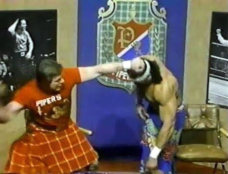 Roddy Piper attacks Jimmy Snuka with a coconut on Piper's Pit