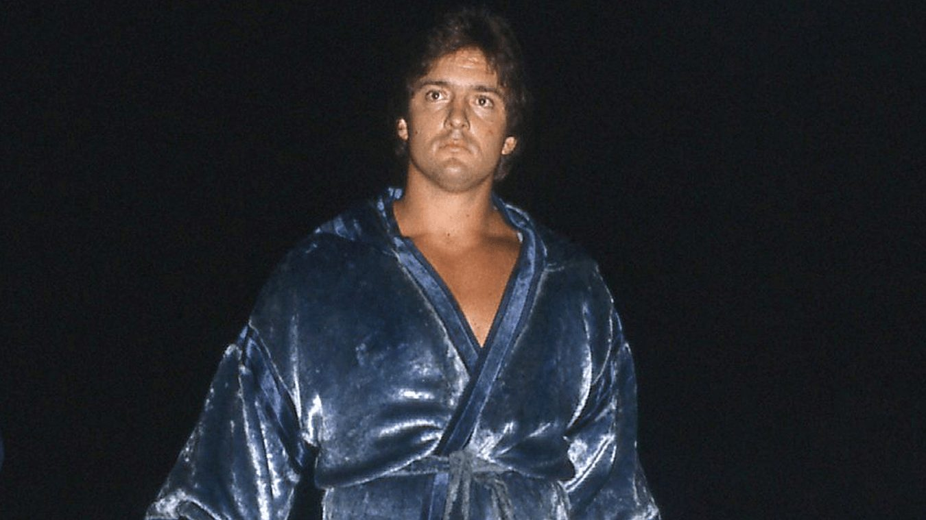 Gino Hernandez wearing a blue robe with a black background