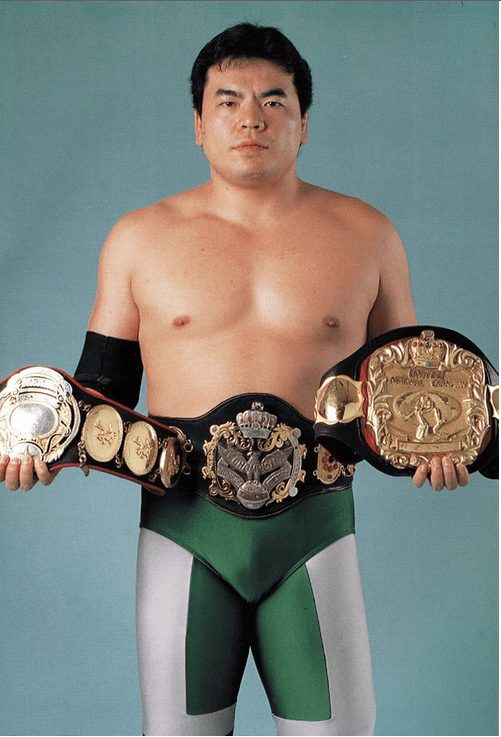 Mitsuharu Misawa in his patented emerald green tights holding all the belts that comprised the Triple Crown Heavyweight Championship: AJWP's most prestigious title.
