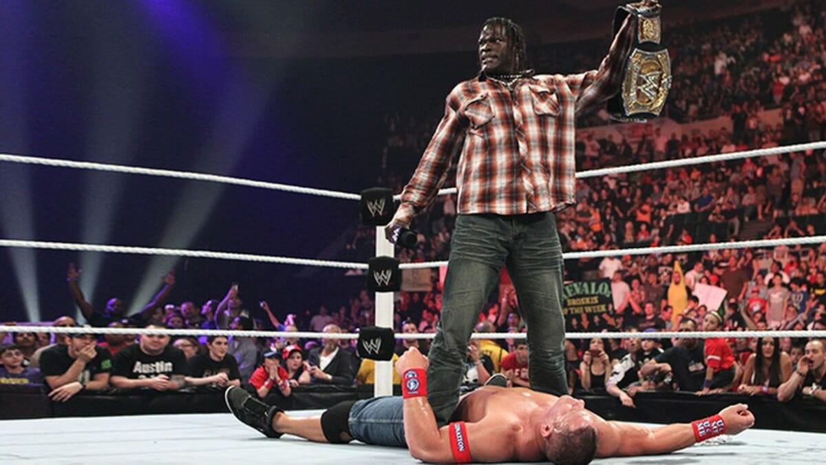 R-Truth stands tall over John Cena with the WWE Championship.