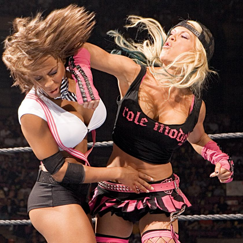 Ashley Massaro, seen here dealing out a vicious forearm to Kristal Marshall (Lashley), started wrestling with no training. She later claimed this led to a litany of physical and neurological problems, addiction to pain medications, and depression.