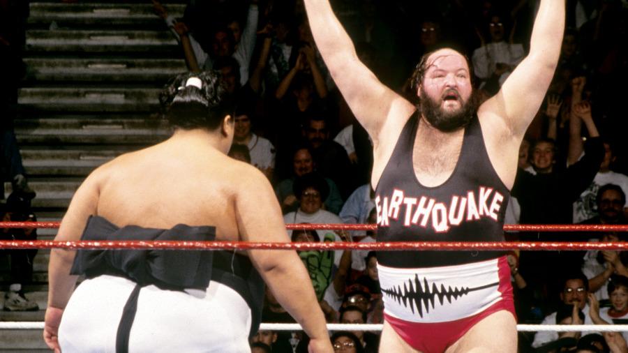 """Earthquake"" John Tenta standing arms raised across the ring from Yokozuna."