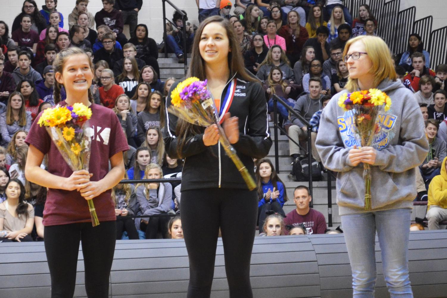 Chelsea Gale, Valerie Tarazi, and Makayla Nietzel stand in recognition for their accomplishments in Cross Country and Swimming at the Fall Honors Assembly on December 1, 2017.