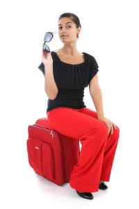 business-traveller-woman-sitting-on-red-suitcase