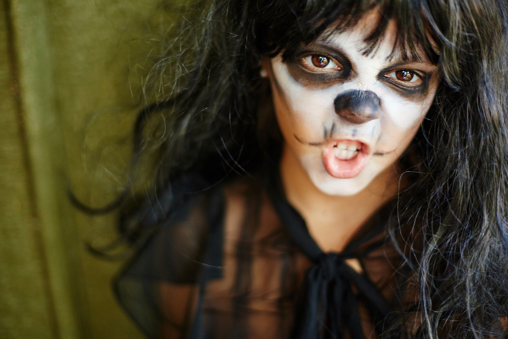 Halloween Kids Face Painting - young girl with witch face paint making expression