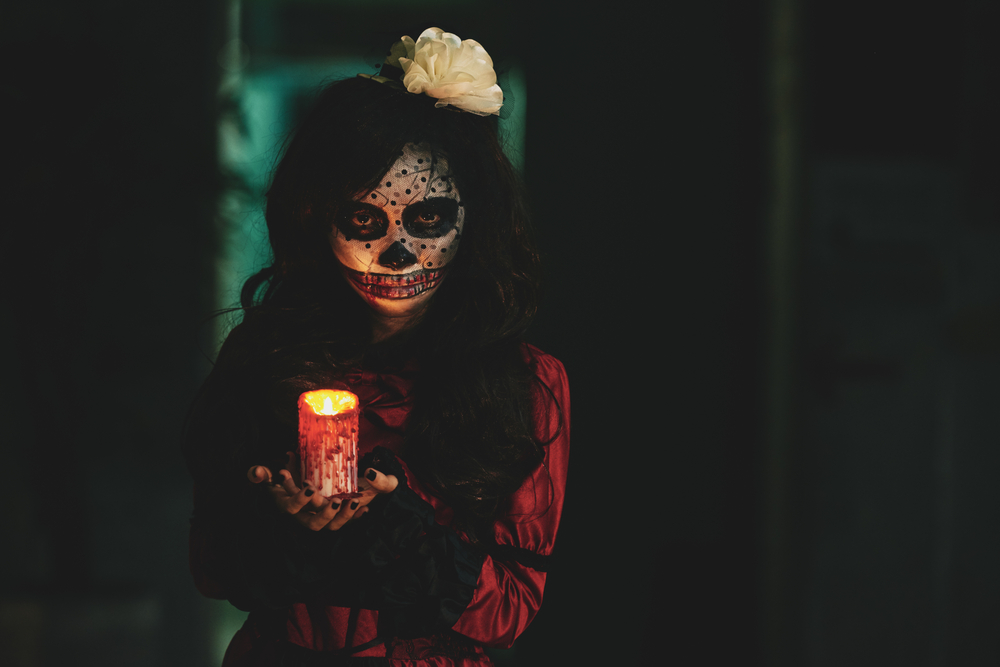 Halloween History - Halloween girl holding glowing candle in dark house