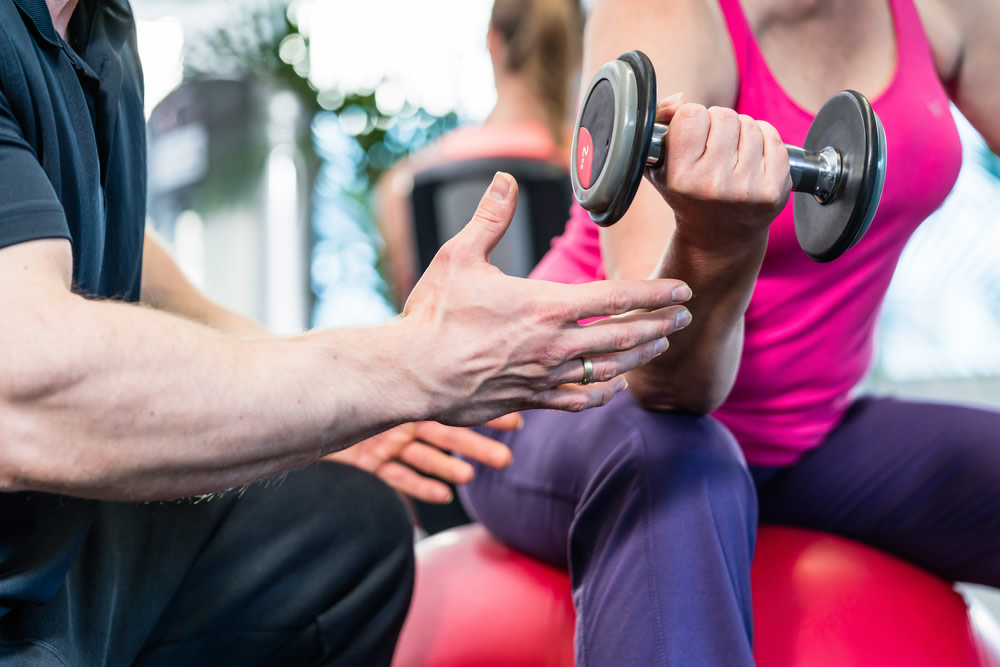 personal trainer muscular arm with weights