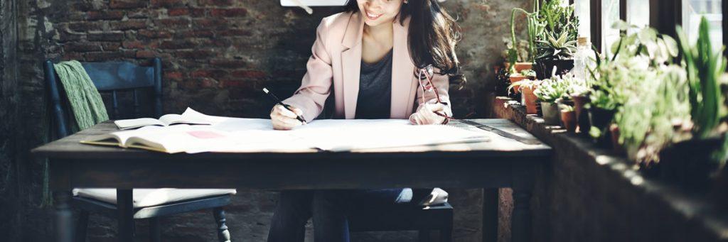 entrepreneur woman in pink jacket at desk doing business