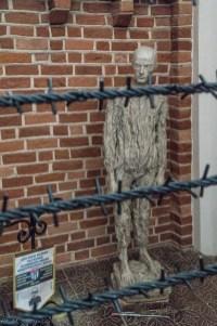 rzeźba człowieka za drutami kolczastymi