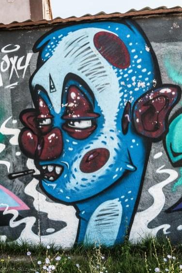 graffiti niebieska twarz z czerwonymi elementami