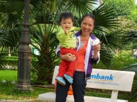 uśmiechająca się kobieta z dzieckiem na rękach w wietnamie