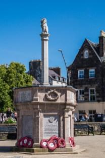 pomnik z wieloboczną podstawą i lwem na kolumnie