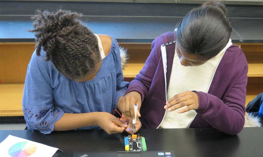 two girls working together on a robotics project
