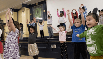 ps8 students dancing in mouse ears in the auditorium