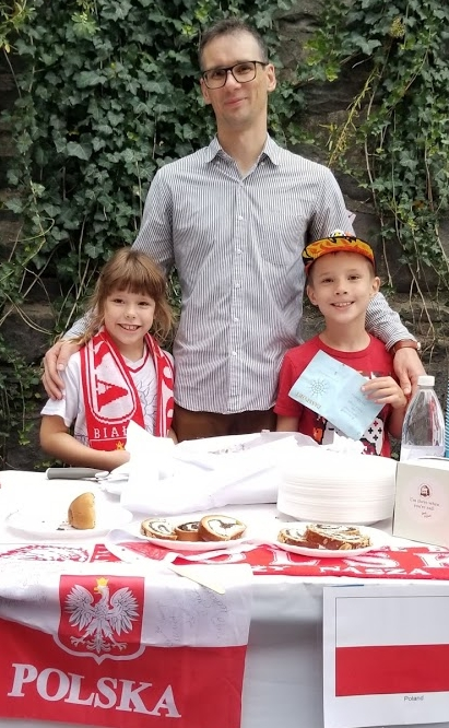 Dad and his two children posing proudly with food from Poland