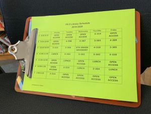 Clipboard with the library schedule on it