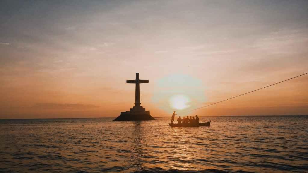 photo of cross in an ocean during dawn