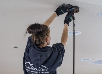 P.S. Electric, Inc. - Female Electrician Installing Hanging Ceiling Light Fixture