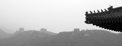 A roof line silhouetted with the Wall in the background. No, that's not fog, it's pollution.