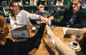people joining hands over a conference table in a business meeting