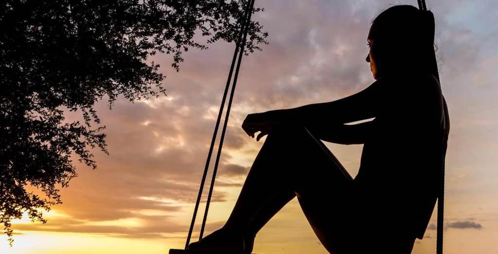 imagem de uma mulher de meia idade, sentada em um balanço, à beira da praia, contemplando o pôr do sol, e refletindo sobre sua vida, sobre o que é psicoterapia e sobre as transformações necessárias em sua própria vida.