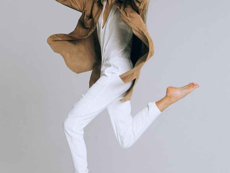 fashionable woman jumping on white background