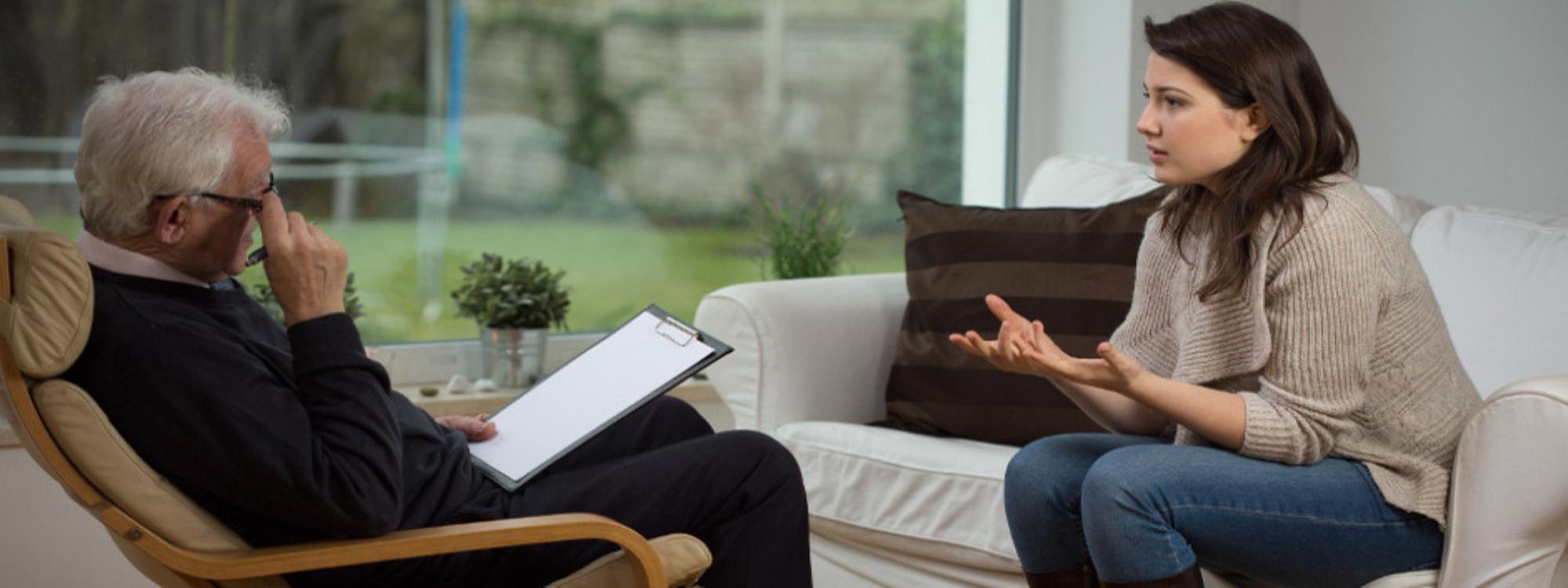 Foto de chica joven sentada en un sofá, hablando con un psicólogo mayor sentada en una butaca.