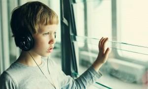 Niño con autismo mirando fuera de la ventana