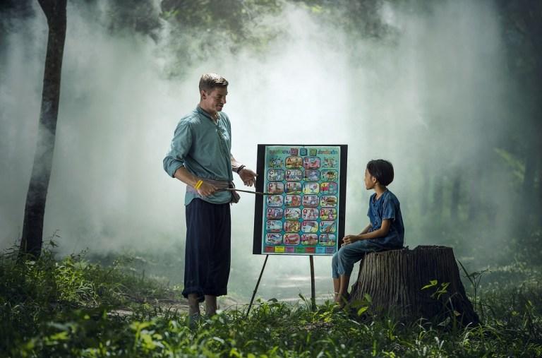 Foto de un maestro y su alumno en un bosque con niebla mirando una pizarra a lado de un tronco.