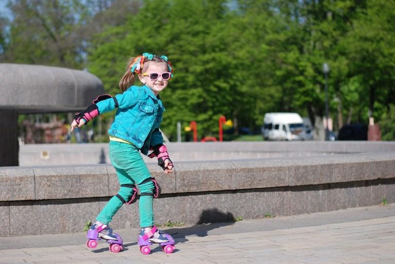 Foto de niña con gafas en el parque con patines.
