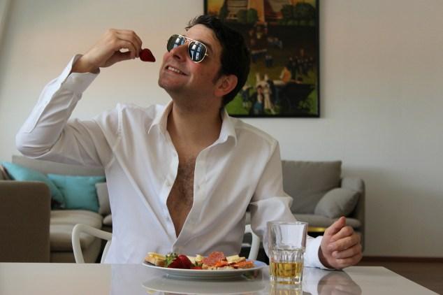 Foto de hombre con camisa blanca, sentado en un mesa, desayunando y poniéndose en la boca una fresa.