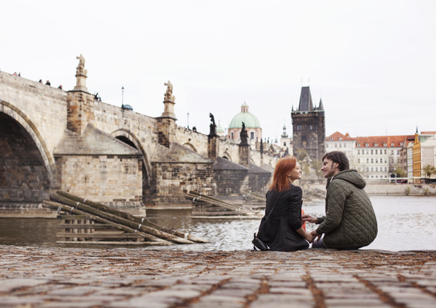 Dos jóvenes enamorados sentados a la orilla de un río cerca de un puente en París.
