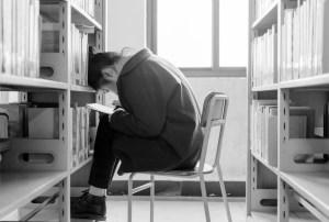 Foto de chica en una biblioteca sentada delante de una estantería con la cabeza apoyada en ella.