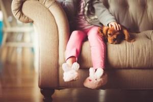 Niña sentada en el sofá acariciando su perro.