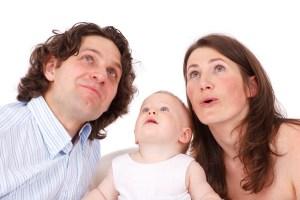 Foto de un bebé con su padres buscando algo con los ojos.