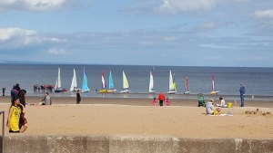 dinghy sailors getting ready to launch from the beach