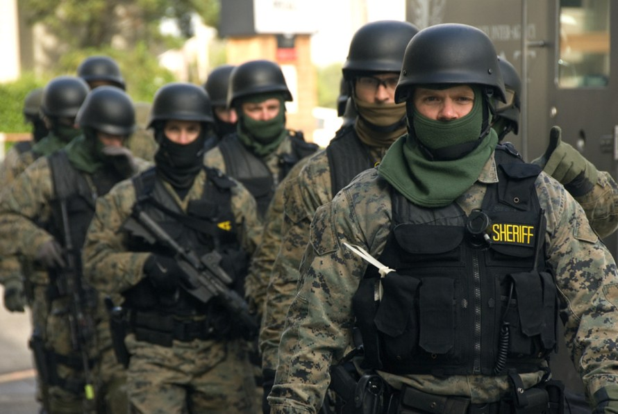 SWAT team members, some armed with assault rifles, prepare for an exercise.