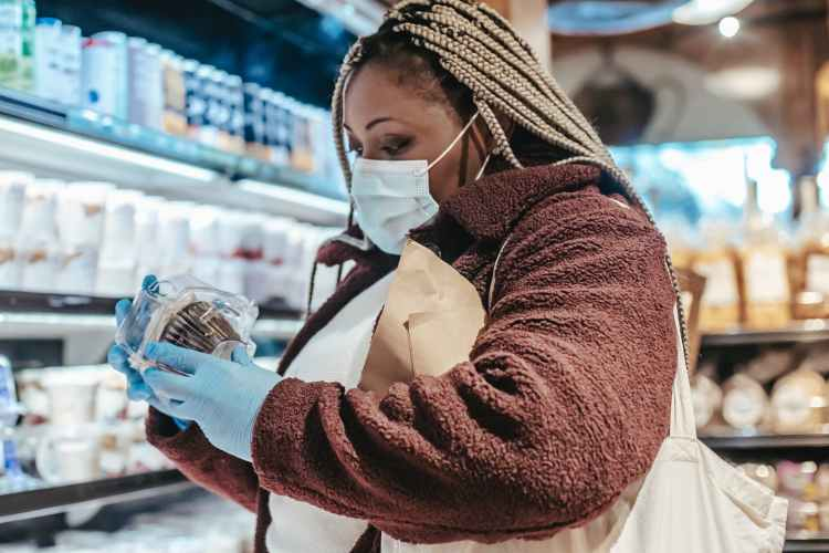 black female shopper reading label on food in supermarket