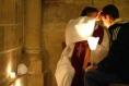 Un confesseur avec une étole violette donne l'absolution en marquant le front du pénitent d'un signe de croix.