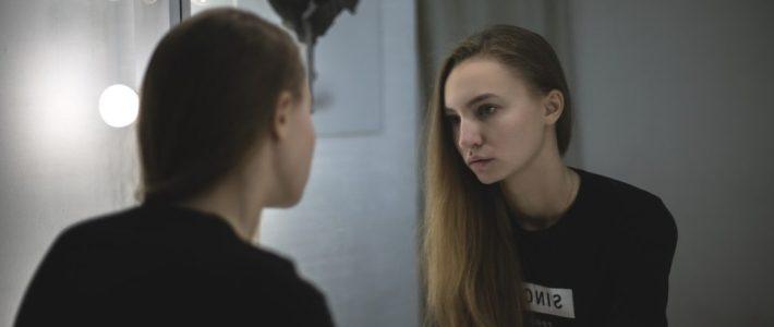 dysmorphophobie: une adolescente devant son miroir