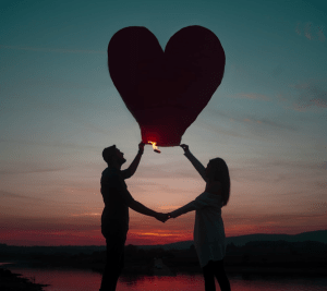 a couple holding a heart shaped lantern balloon against a pink and blue sunset