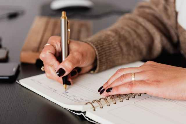 crop woman writing down notes in diary