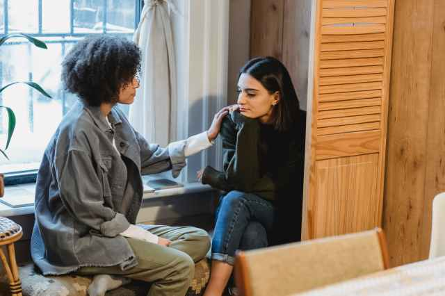 young ethnic woman supporting upset female friend at home