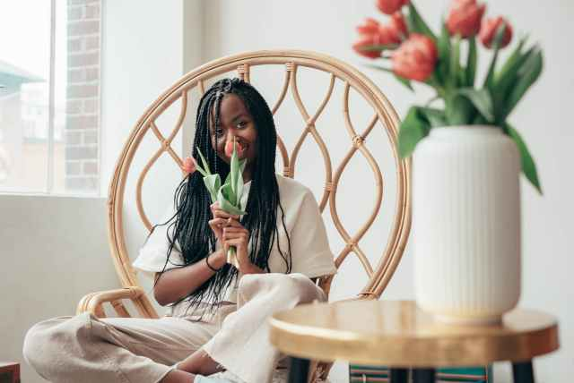 smiling young black lady smelling bunch of tulips while sitting on chair