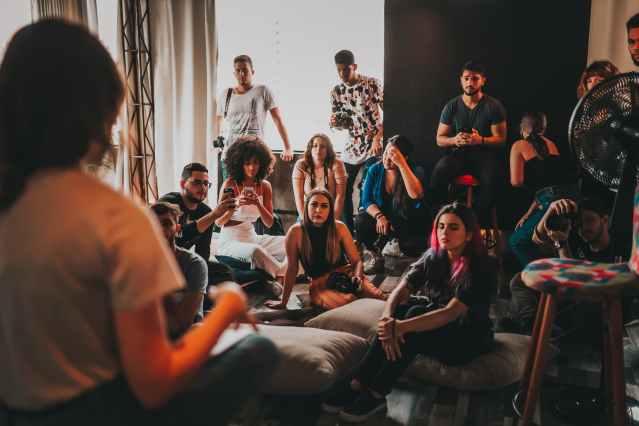 group of multiethnic people gathering around female speaker in studio