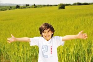 Vrolijke jongen met armen open in zonnig gras. Vergroot het zelfvertrouwen van je kind